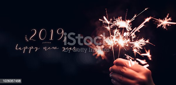 istock Hand holding burning Sparkler blast with happy new year 2019 on a black bokeh background at night,holiday celebration event party,dark vintage tone. 1026357458