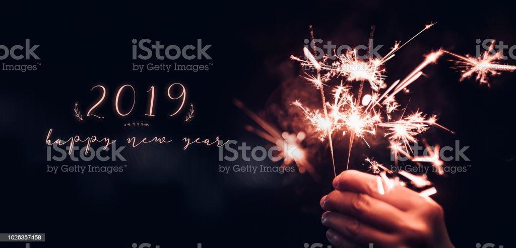 Mão segurando o ardor explosão Sparkler com feliz ano novo 2019 sobre um fundo preto bokeh durante a noite, festa de evento de celebração de Natal, Tom escuro vintage. - foto de acervo
