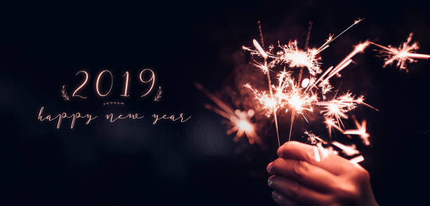 Hand holding burning Sparkler blast with happy new year 2019 on a black bokeh background at night,holiday celebration event party,dark vintage tone. stock photo