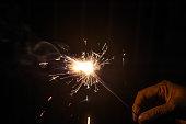 Hand holding burning sparkler during new year celebration.