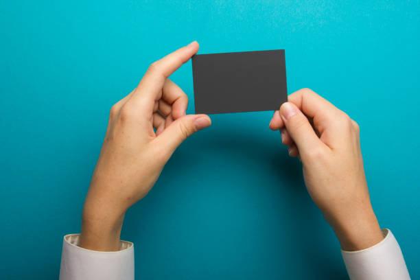 Mão segurando o cartão de visita em branco sobre fundo abstrato - foto de acervo