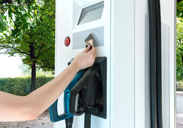 Hand holding calltime refill card or pre-paid card to refill money of charging electric car ( EV ) machine at charging station with nature background. stock photo