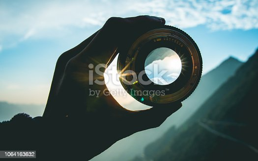 Hand holding camera lens at sunset