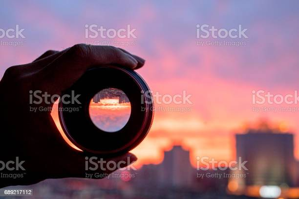 Hand holding camera lens looking at scenics of glowing clouds at picture id689217112?b=1&k=6&m=689217112&s=612x612&h=d0pbdylp0mht6uyrcm2shbxnaooti56h5nunowcmsjs=