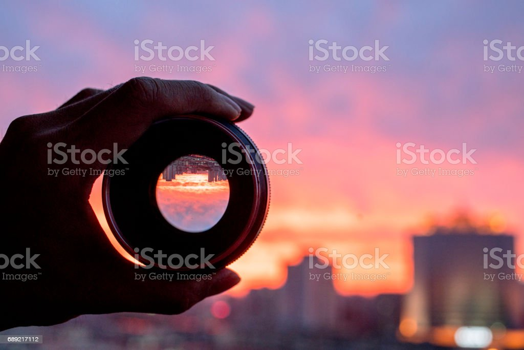 hand holding camera lens, looking at scenics of glowing clouds at sunset stock photo