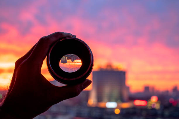 hand holding camera lens, looking at scenics of glowing clouds at sunset - ingrandimento foto e immagini stock
