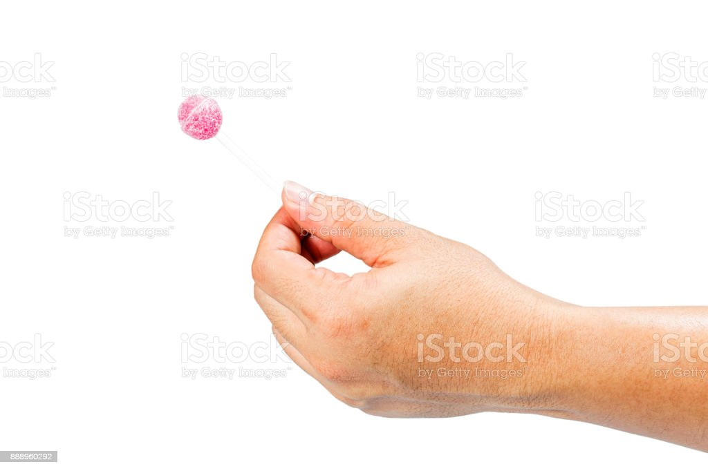 Hand holding candy stick. The gesture is submitting candy. stock photo