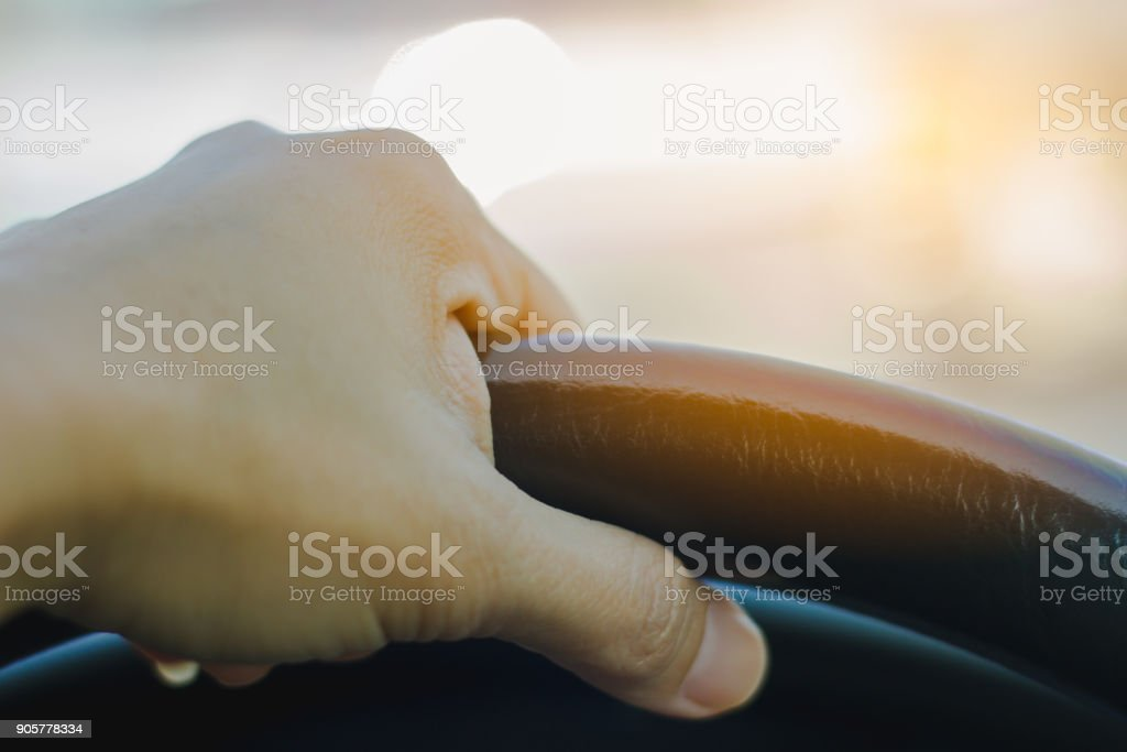 Hand holding car steering wheel stock photo