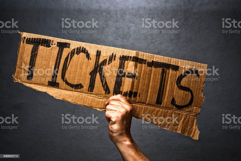 Hand holding cardboard sign with Tickets written on it stock photo