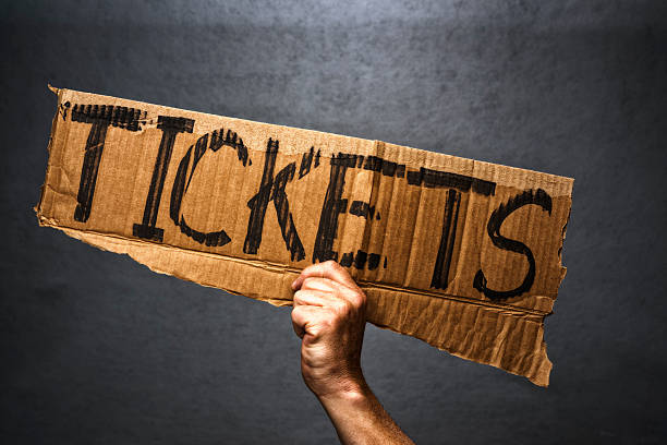 hand holding cardboard sign with tickets written on it - ticket stock photos and pictures