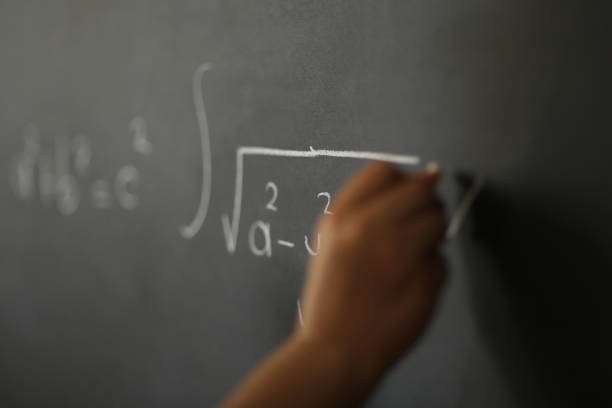 Hand Holding Chalk and Writing Complex and Sophisticated Mathematical Formula/ Equation on the Blackboard. stock photo