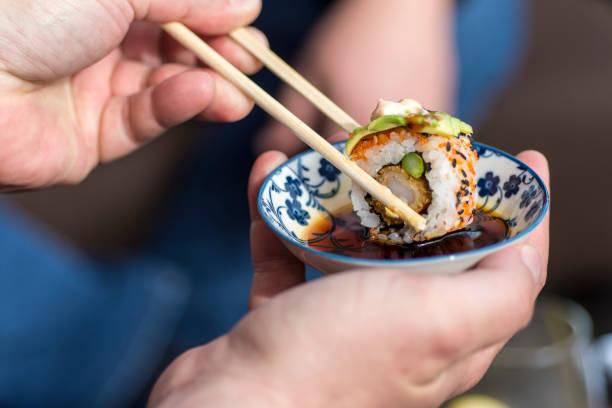hand mit stäbchen sushi-rolle in soja-sauce tauchen - sushi essen stock-fotos und bilder