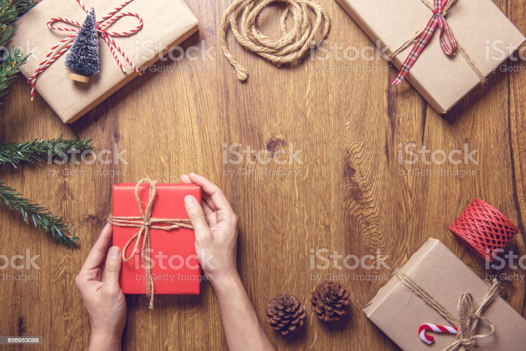 Hand holding Christmas gift box and tree branch decor on wooden table background. stock photo