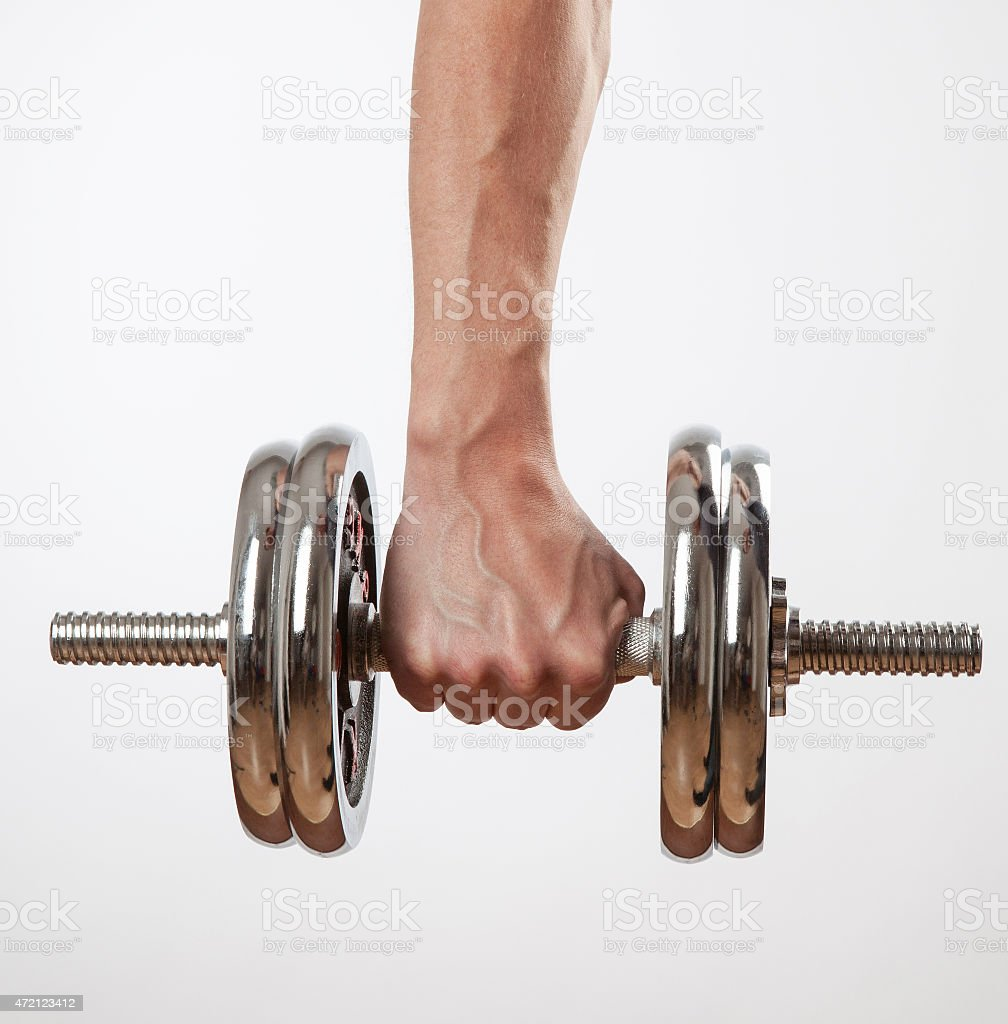 Hand holding chrome dumbbell on the white background. stock photo
