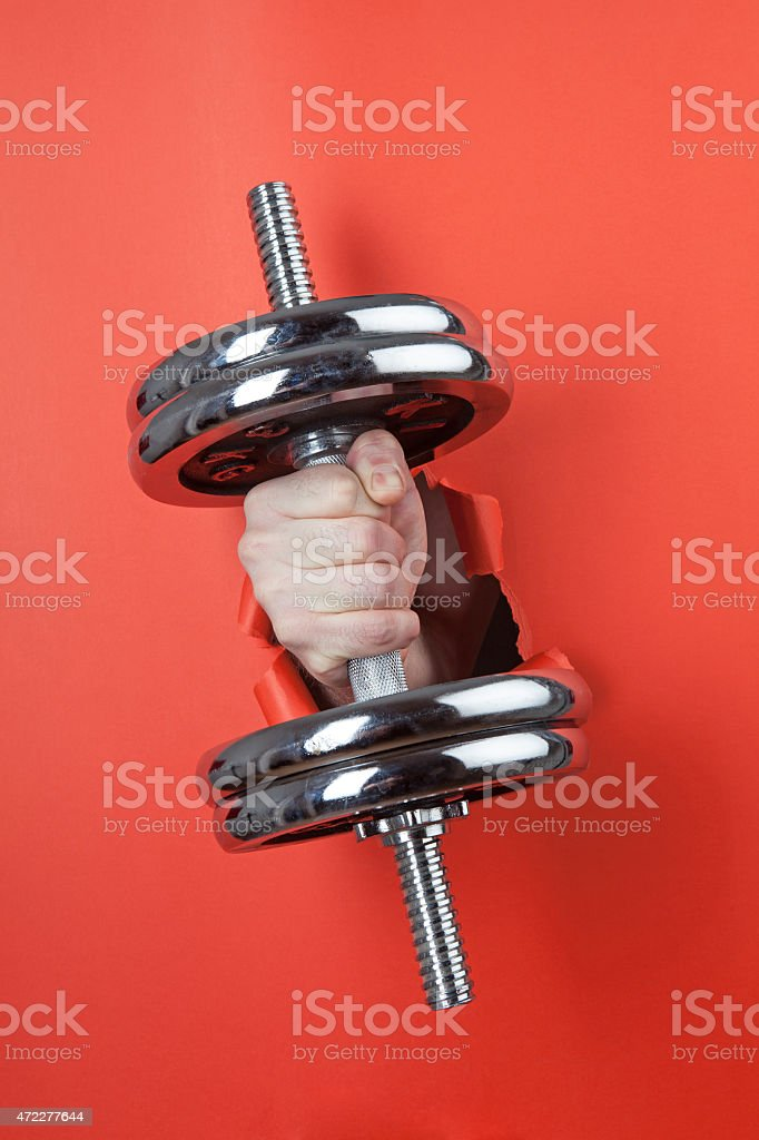 Hand holding chrome dumbbell through hole on the red paper. stock photo