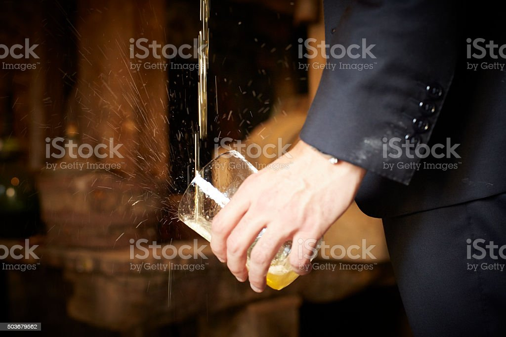 Mano sosteniendo vaso de sidra que está siendo escanciada - foto de stock