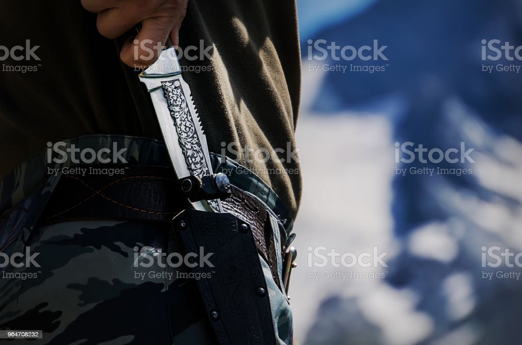 Hand holding classic knife with sheath for hunter who love camping or hiking royalty-free stock photo