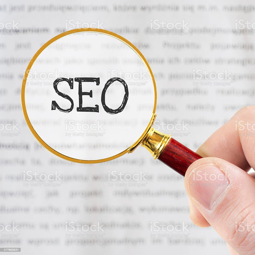 Hand holding classic styled magnifying glass, with SEO sign royalty-free stock photo