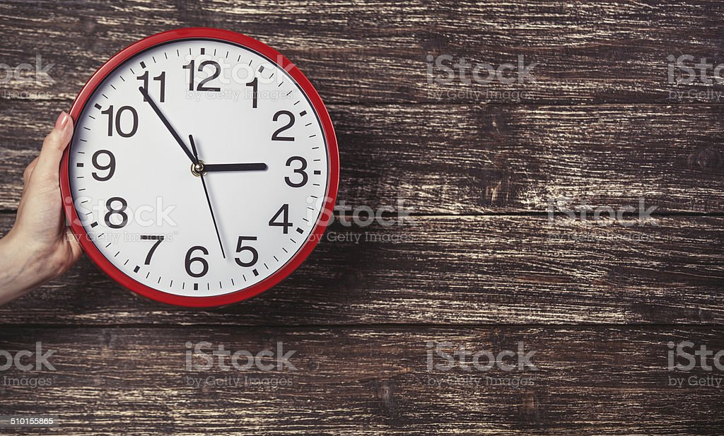 Hand holding clock on wooden background. stock photo