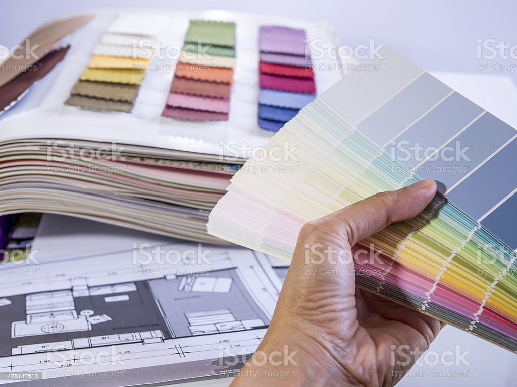 Hand holding color samples with interior furniture plan royalty-free stock photo