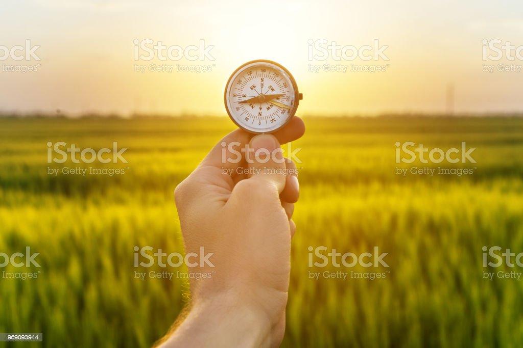 brújula de mano holding y arroz campo sunset foto de stock libre de derechos