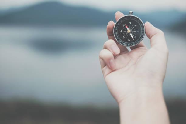 Hand mit Kompass für die Suche Richtung im Freien. Mann sucht Weg mit Natur Hintergrund. Reisen Sie, Lifestyle, Sommer Urlaub Konzept – Foto