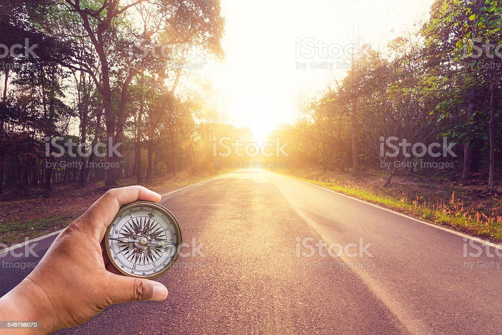Hand holding compass on empty asphalt road and sunset. stock photo