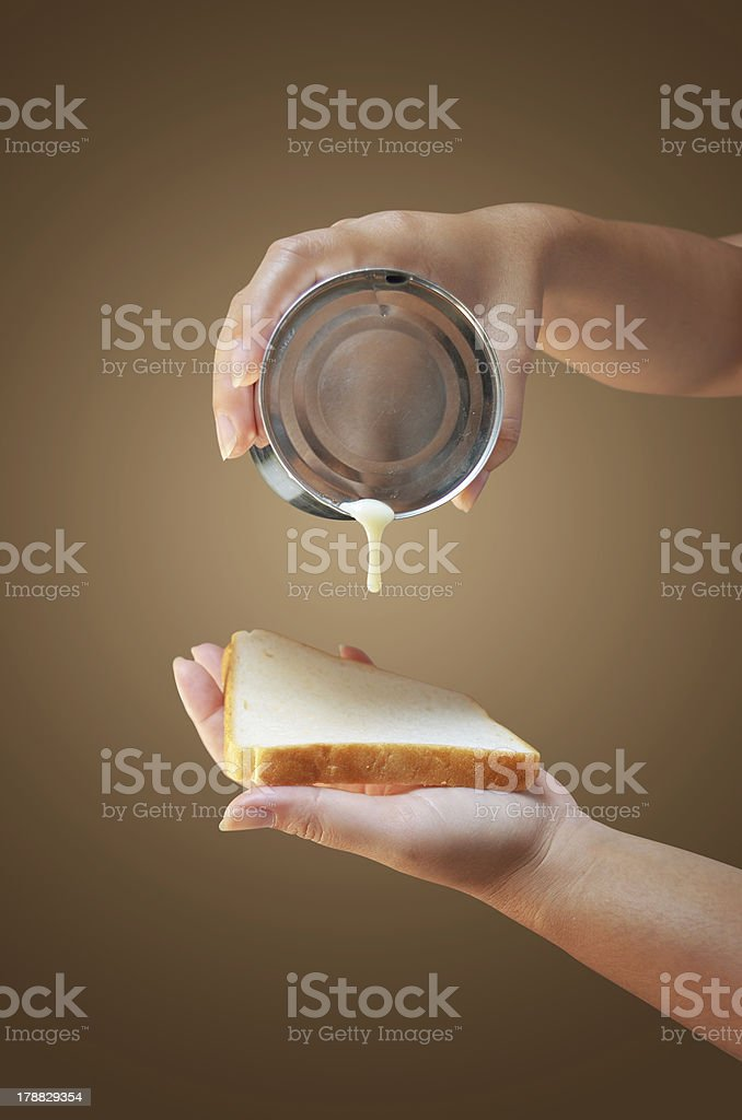 hand holding condensed milk can with bread stock photo