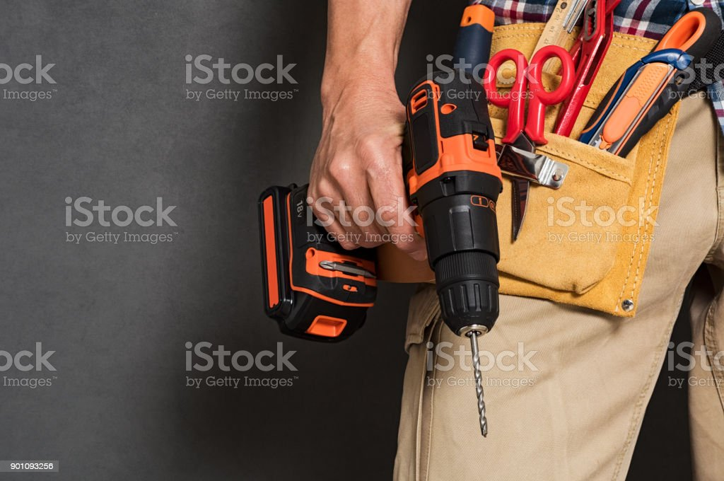 Hand holding construction tools Close up of handyman holding a drill machine with tool belt around waist. Detail of artisan hand holding electric drill with tools isolated over grey background. Closeup hand of bricklayer holding carpentry accessories. Adult Stock Photo