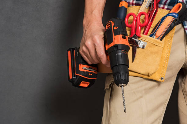Hand holding construction tools Close up of handyman holding a drill machine with tool belt around waist. Detail of artisan hand holding electric drill with tools isolated over grey background. Closeup hand of bricklayer holding carpentry accessories. drill stock pictures, royalty-free photos & images