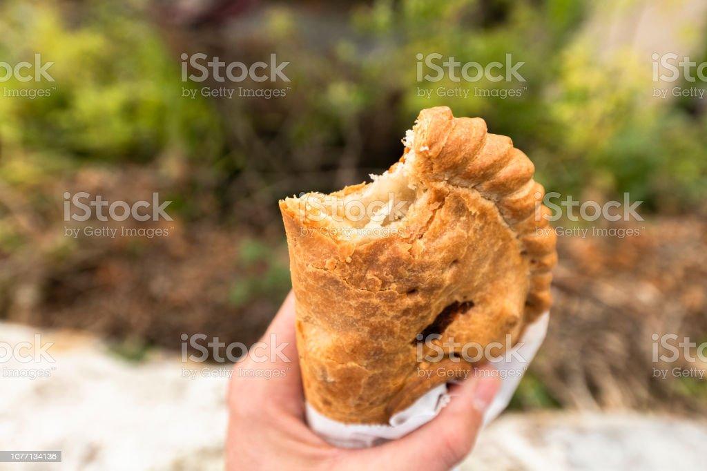 POV hand holding Cornish pasty in Charlestown, Cornwall stock photo
