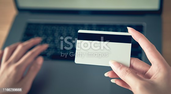 1016971522 istock photo Hand holding credit card and press laptop computer enter the payment code for the product. Pay online for convenience. 1166299668