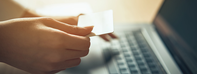 istock Hand holding credit card and press laptop computer enter the payment code for the product. Pay online for convenience. 1167580089