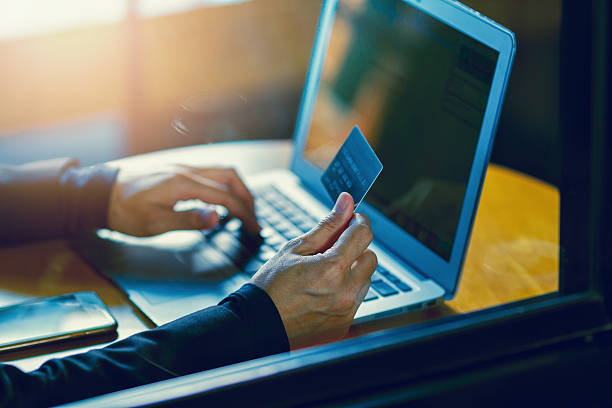 hand holding credit card and shopping online by laptop - paid stock pictures, royalty-free photos & images