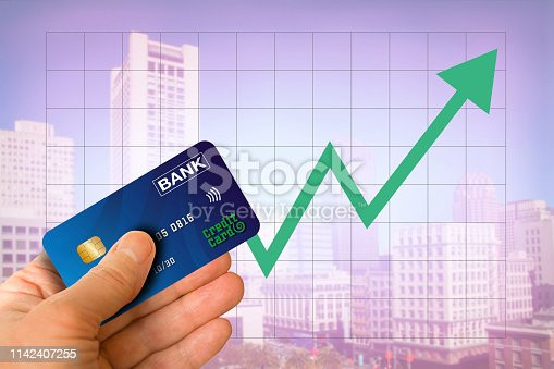 istock Hand holding credit card from bank with cityscape and green arrow going up showing real estate market economy going up with blurred office buildings in the background 1142407255