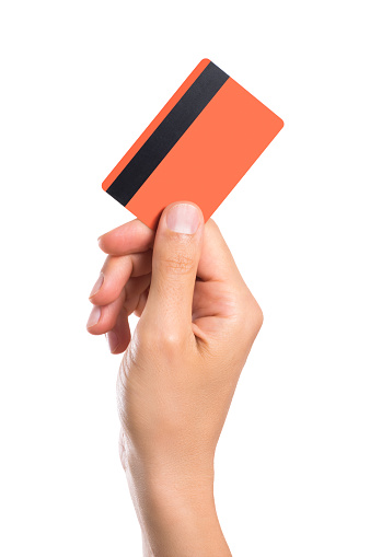 Hand holding credit card isolated on white background. Close up of a man hand holding up a creditcard. Male hand showing orange credit card with magnetic strip.