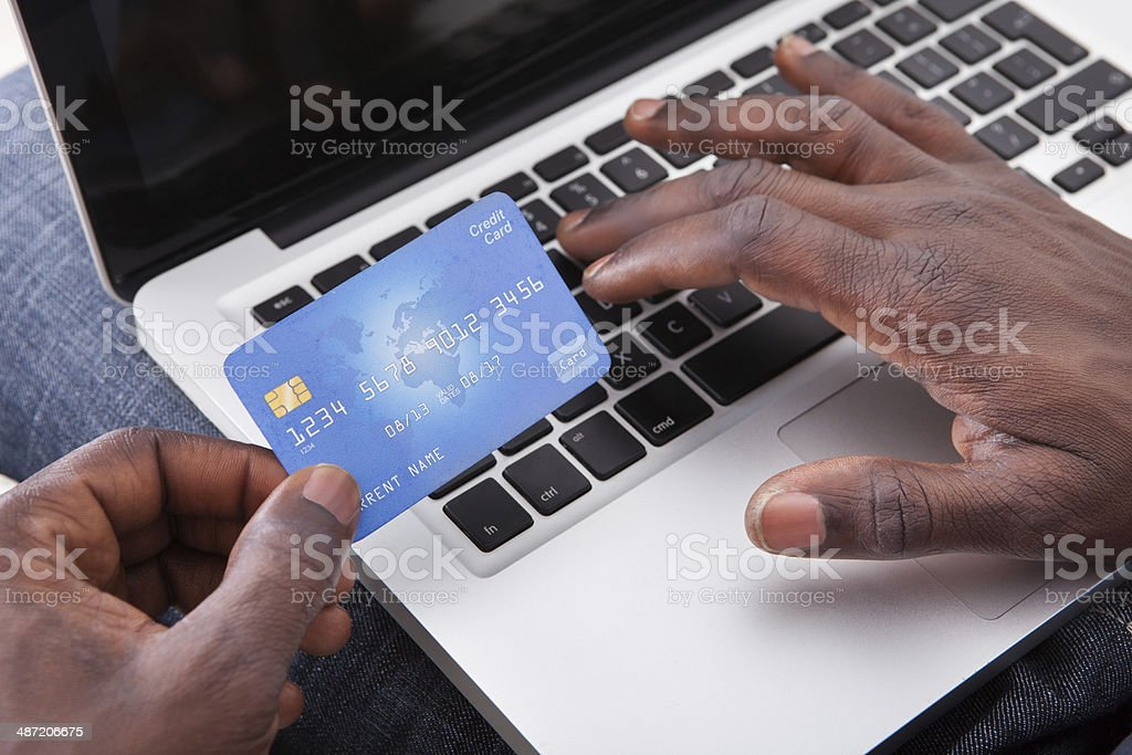 Hand Holding Credit Card With Laptop stock photo