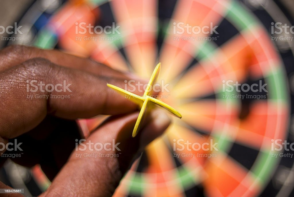 hand holding dart getting ready to throw on dartboard royalty-free stock photo