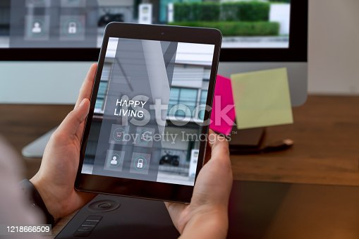 Hand holding digital tablet and using computer with showing website for rent and sale of houses online.