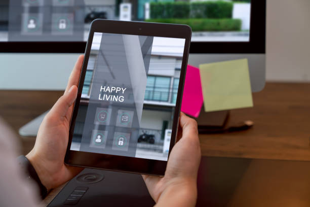 Hand holding digital tablet and using computer with showing website for rent and sale of houses online. stock photo