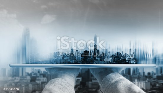 1082409706 istock photo Hand holding digital tablet with futuristic modern buildings hologram on screen 922733870