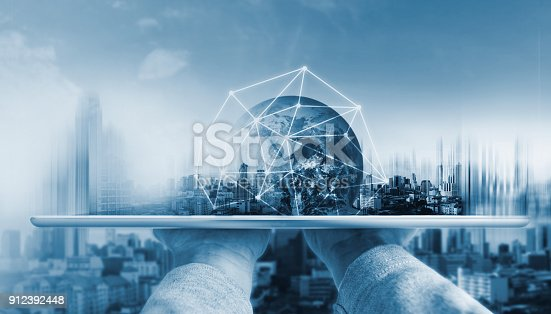 istock Hand holding digital tablet with global network connection technology and modern buildings. Element of this image are furnished by NASA 912392448
