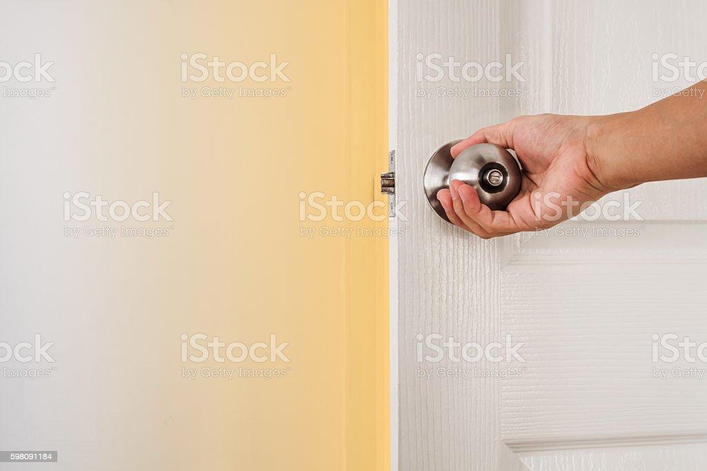Hand holding door knob, white door and wall stock photo