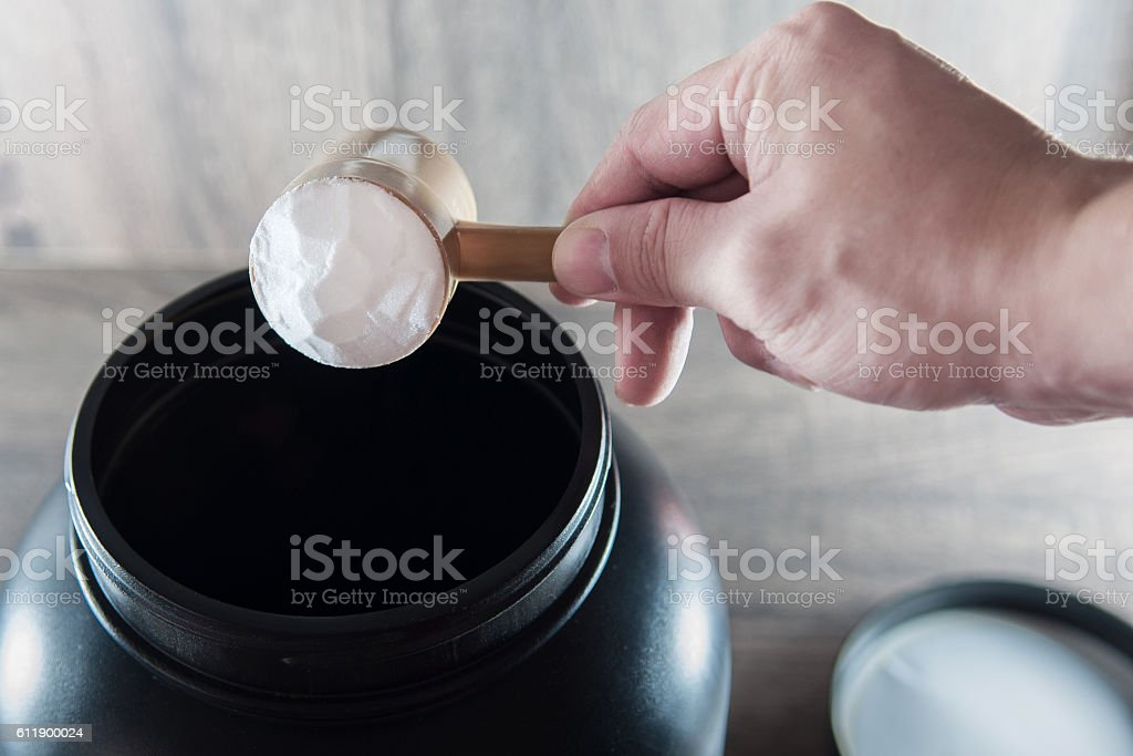 Hand holding doser and pouring food supplement stock photo