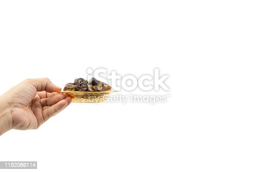 982465812 istock photo Hand holding dried dates fruits isolate on white. 1152086114