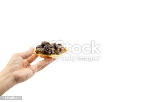 982465812 istock photo Hand holding dried dates fruits isolate on white. 1152086122
