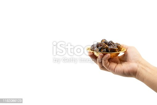 982465812 istock photo Hand holding dried dates fruits isolate on white. 1152086123
