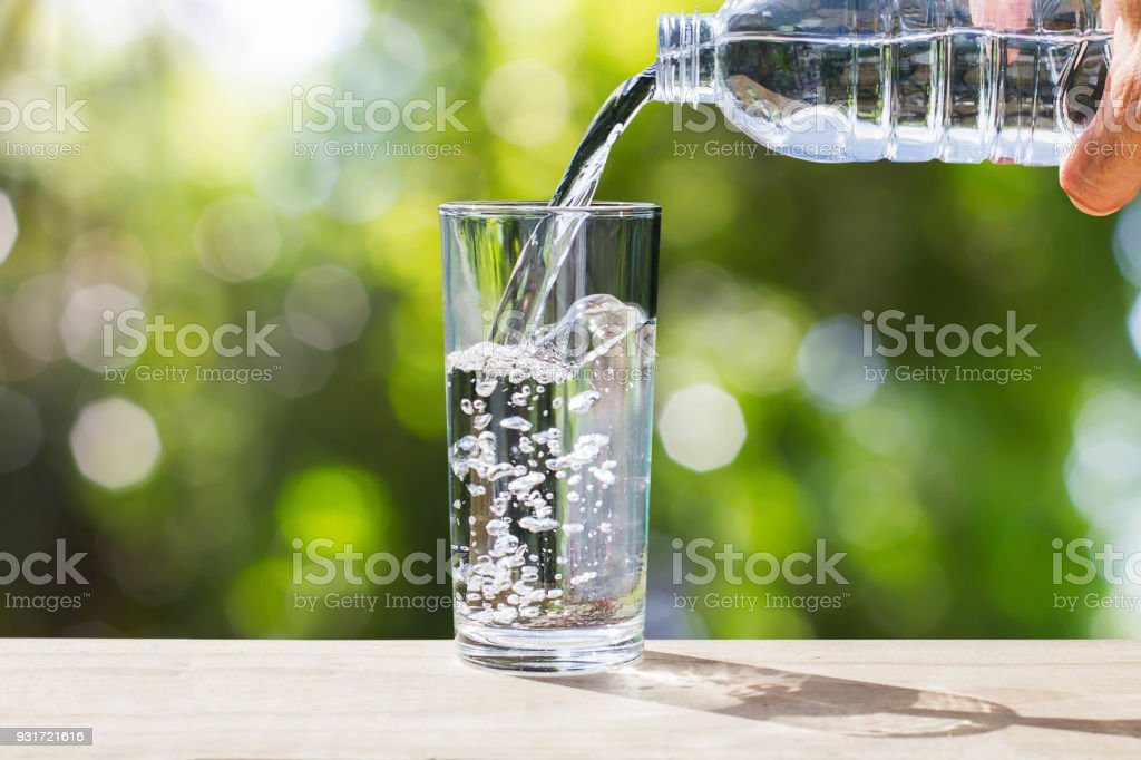 Hand holding drinking water bottle pouring water into glass on wooden...