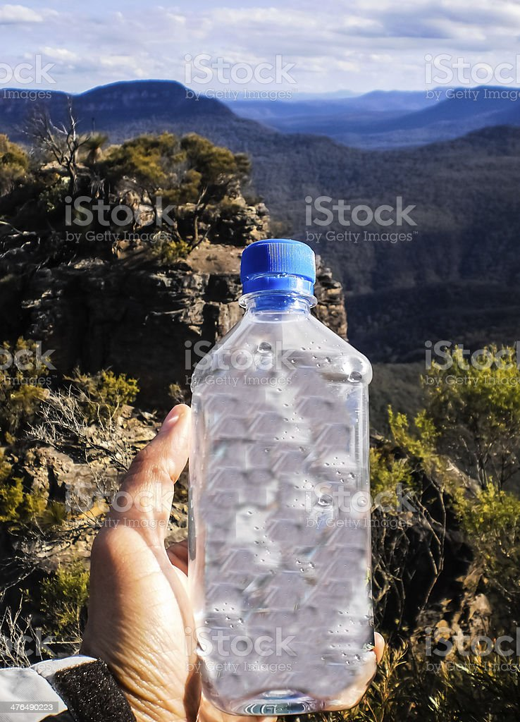 Hand holding drinking water on mountain background stock photo