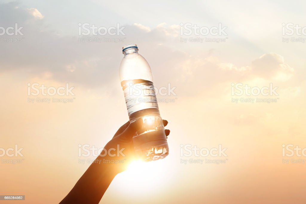 hand holding drinking water on sunset background stock photo